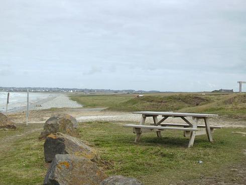 Blick auf den Strand und den Kieselsteinwall am Ufer. Im Hintergrund der Ort Penhors.