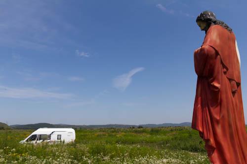 Letzte Mittagspause im Feld. Eine Jesus-Skulptur steht mitten im Grünen und wacht über uns