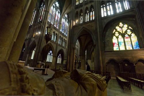 Blick vom linken Seitenschiff über einen Sarkophag zurück in das Langhaus. Rechts eins der Chagall-Fenster