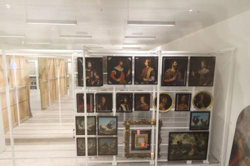 Blick ins Depot, die Gemälde teils mit Pflasterstreifen im Gesicht.